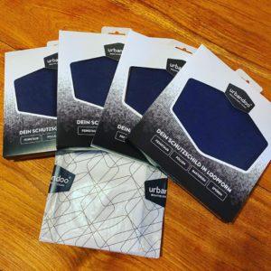 Vier Päckchen mit schwarzen Urbandoo-Loops und ein Päckchen mit Austausch-Filter-Inlays FFP3
